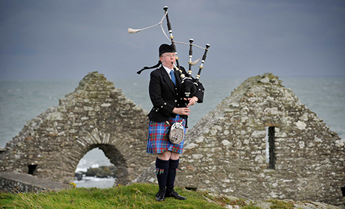 Photo of a piper in Scottish dress in front of an old stone building