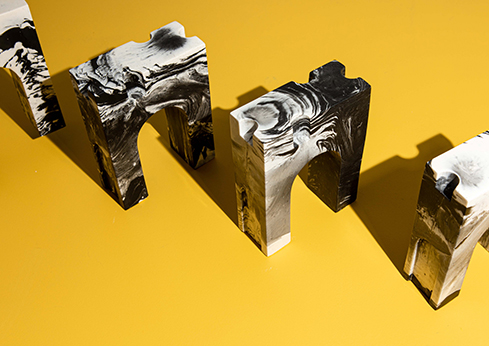 Photo of Triumph by Rehka Barry, black and white marble trophies in the shape of L'Arc de Triomphe, on an orange background
