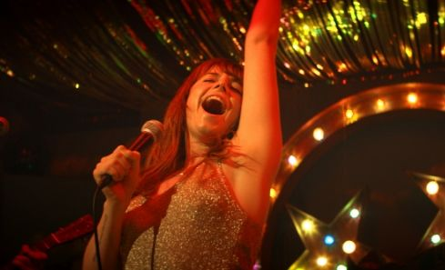 Jessie Buckley sings into a microphone in Wild Rose
