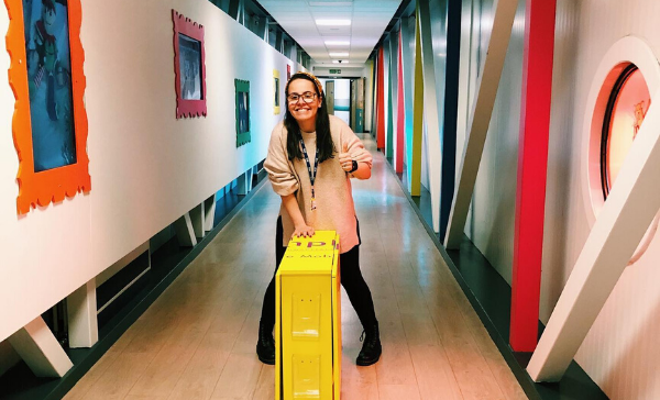 A woman pushes a yellow box on wheels down a colourful hallway - she is smiling at the camera