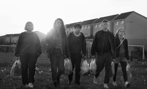 A group of young people walk through a park in the film BEATS