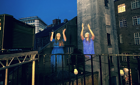 Photo of a building at night with two women projected onto it, doing sign language