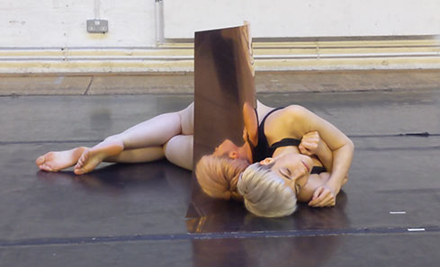 Laura Fisher in FORGED. Laura is laying on her side curled around an upright copper tube